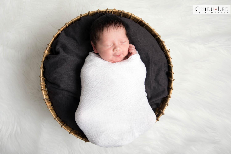 Full body newborn baby boy sleeping eyes closed white wrap on wicker braided round circular basket with black cushion