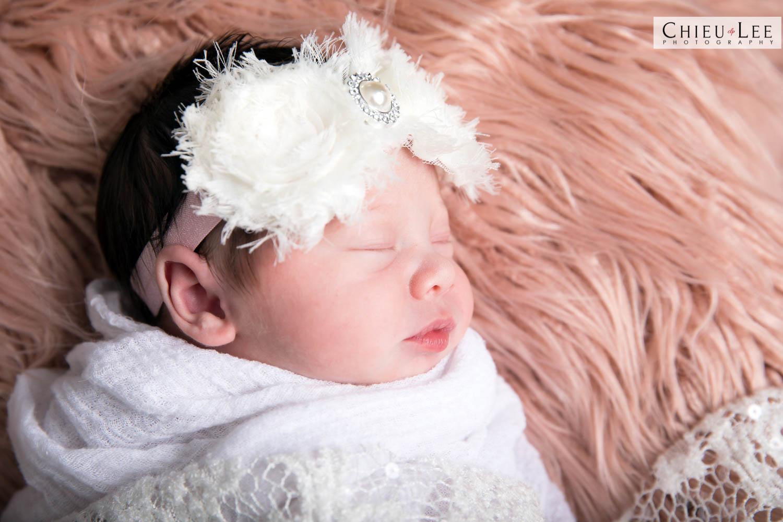 Closeup newborn baby girl sleeping eyes closed white flower lace headband and white wrap on brown tan fur