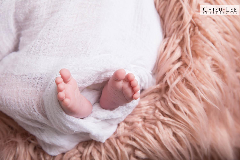 Closeup newborn baby girl feet white wrap on brown tan fur