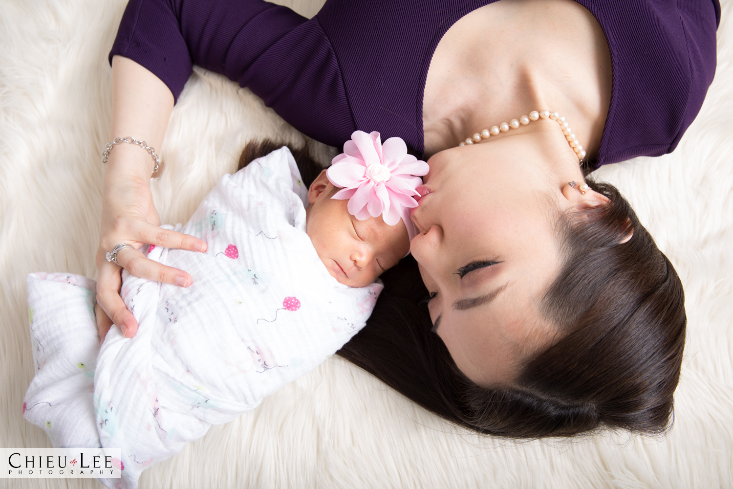Mother mom and child newborn baby girl embrace forehead kiss closeup two shot pink flower headband and white wrap sleeping eyes closed purple blouse pearl necklace on ivory blanket