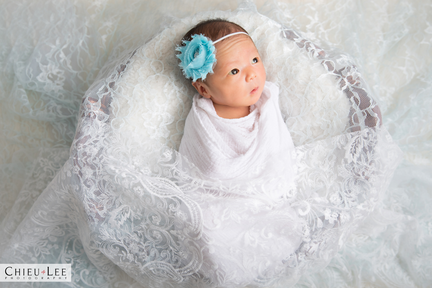 Newborn baby girl awake eyes open full body teal blue green turquoise headband with white wrap on white lace and white blanket