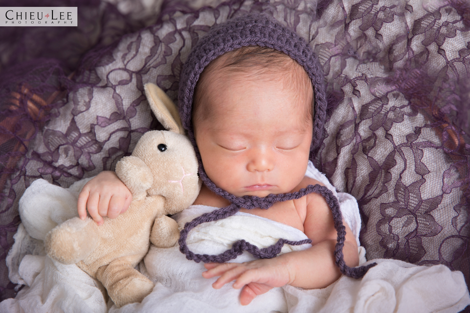 Newborn baby girl half body sleeping eyes closed purple crochet bonnet and white wrap cuddling beige plush bunny doll on purple lace and white blanket