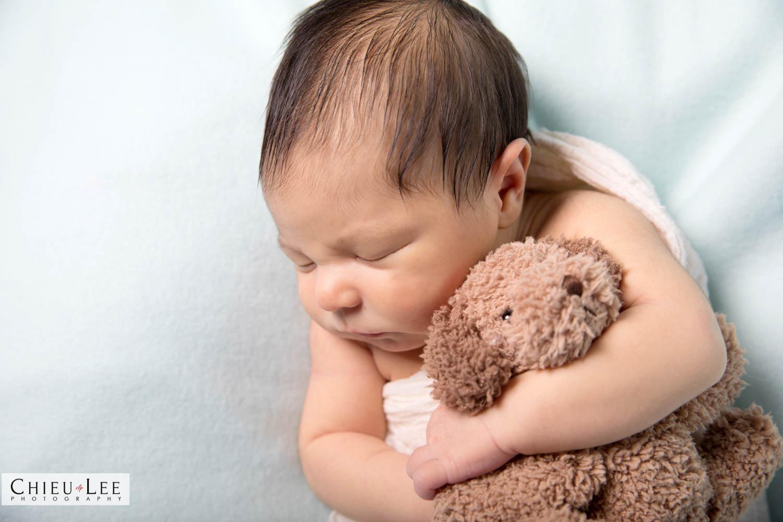Closeup newborn baby boy sleeping eyes closed white wrap cuddling holding hugging plush puppy doll toy on white blanket